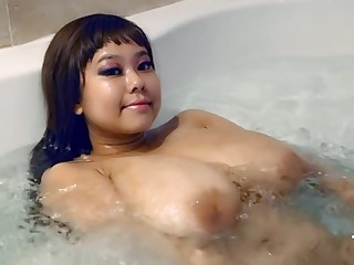 Asian pamper with huge melons in the bathtube